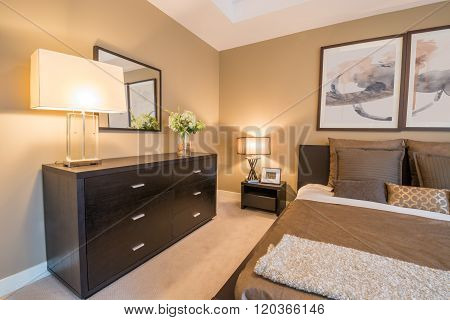 Modern bright bedroom interior with a large dresser and mirror.