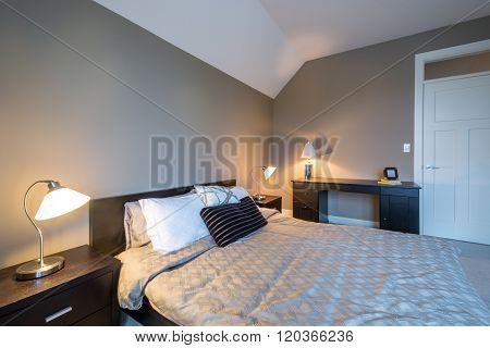 Modern bright bedroom interior design with night tables and office desk.