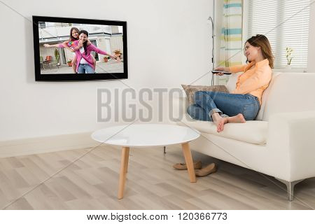 Woman Sitting On Sofa Watching Television