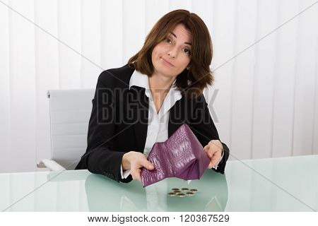 Businesswoman Holding Empty Purse With Euro Coins At Desk