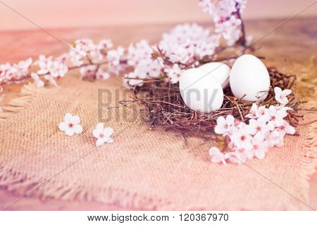 Pink spring flowers and white Easter eggs in nest