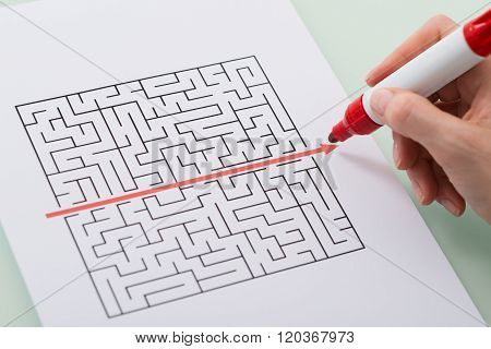Woman Hand Drawing Straight Red Line Over Maze