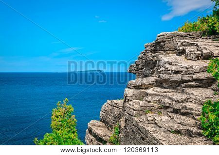Natural rocky cliff landscape view above tranquil azure blue water at beautiful Bruce Peninsula