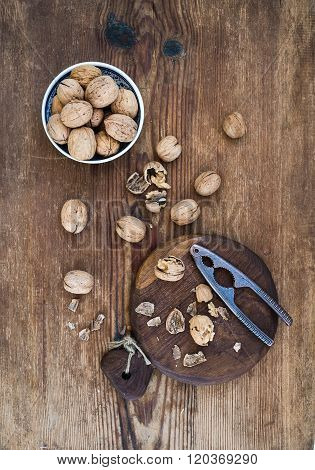 Walnuts in ceramic bowl and on cutting board with nutcracker over  rustic wooden background, top vie