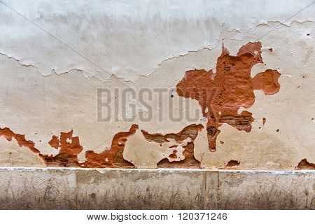 Architectural Detail of Chipped Wall - Red Stone Wall Painted White with Large Erosed Chips and Cracks in Surface