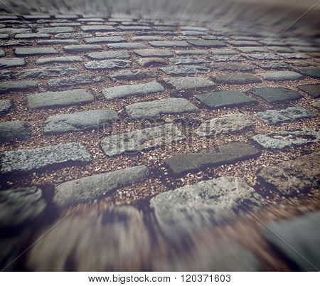 Close up of old worn out brick paving blocks separated by stones in road with blurry edges simulating motion