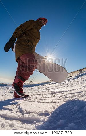 Snowboarder Walking Against Blue Sky