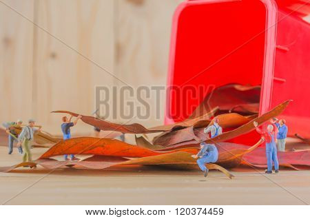 Image Of Mini Figure Dolls Worker Collect Dry Leaves Into The Red Recycle Bin .