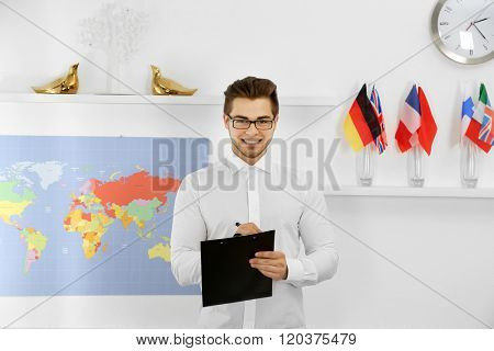 Happy young man with pen and paper holder in the office of travel company