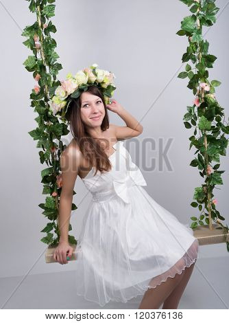 Beautiful young leggy blonde in a little white dress on a swing, wooden swing suspended from a rope