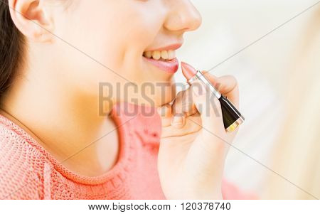 beauty, make up, cosmetics and people concept - close up of smiling young woman face and visagist hand applying lipstick