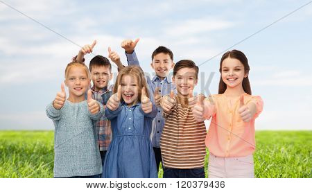 childhood, fashion, summer, gesture and people concept - happy smiling children showing thumbs up over blue sky and grass background