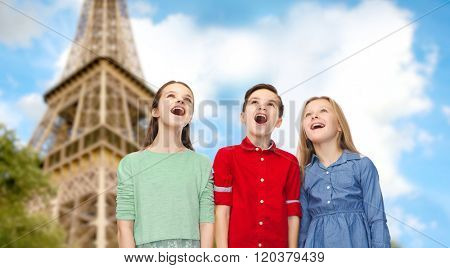childhood, travel, tourism, friendship and people concept - happy amazed boy and girls looking up with open mouths over paris eiffel tower background