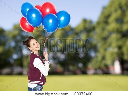 people, teens, holidays and party concept - happy smiling pretty teenage girl with helium balloons over summer park background
