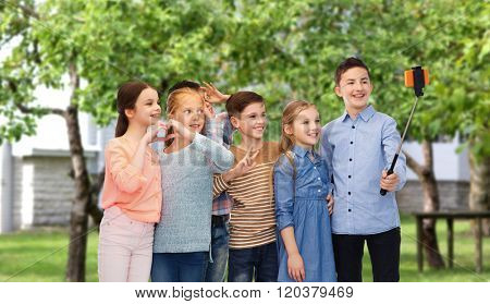 childhood, friendship, technology and people concept - happy children talking picture by smartphone on selfie stick over private house backyard background