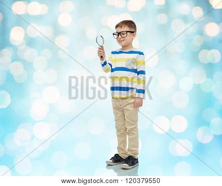 childhood, education, investigation, discovery and people concept - happy little boy in eyeglasses with magnifying glass over blue holidays lights background