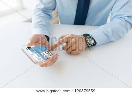 business, technology, mass media and people concept - close up of male hand holding and showing transparent smart phone and watch at office with news web page on screen