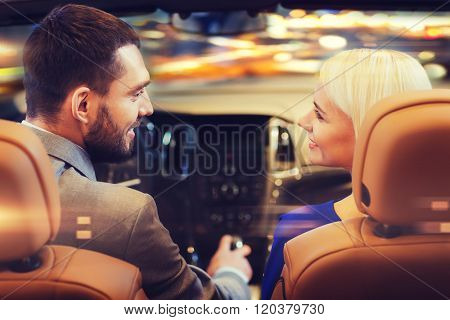 love, luxury, nightlife, automobile  and people concept - happy couple driving in cabriolet car over night city lights background