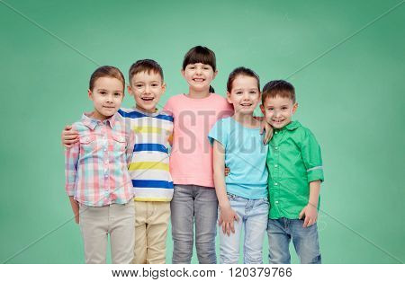 childhood, preschool education, friendship and people concept - group of happy smiling little children hugging over green school chalk board background