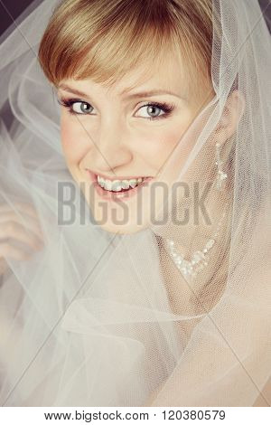Vintage style portrait of young beautiful happy smiling bride with bridal veil