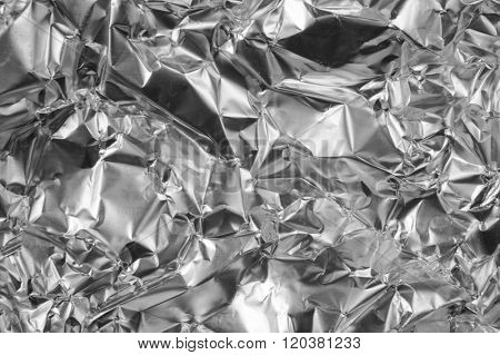Silver foil background with shiny crumpled uneven surface for texture and background