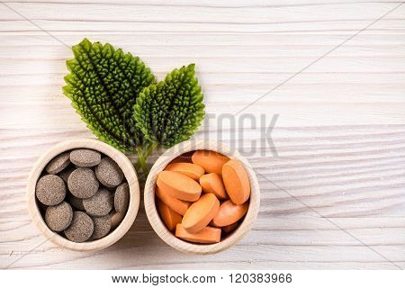Homeopathic Pills In Containers With Green Leaves