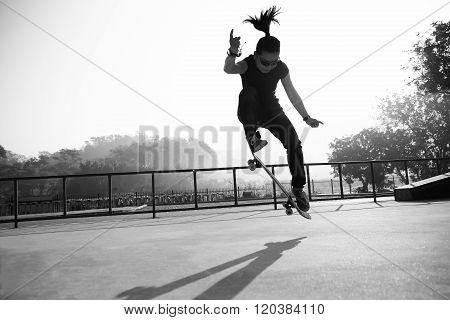 young woman skateboarder skateboarding at sunrise skatepark