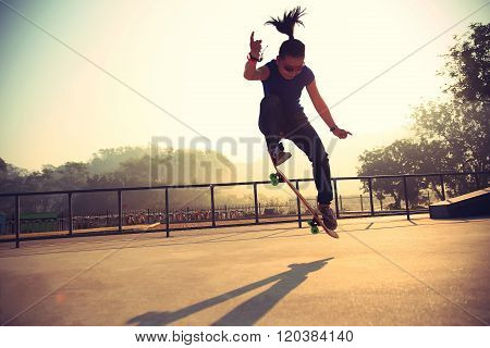 young woman skateboarder skateboarding at sunrise skatepark