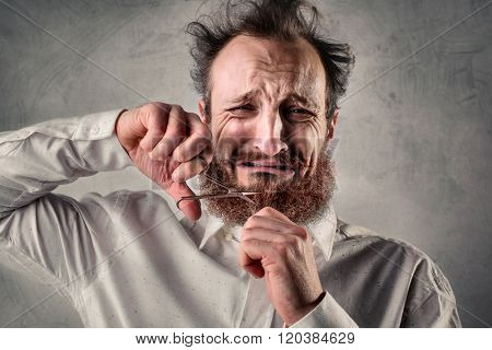 Desperate man cutting his beard