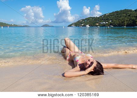 Young Woman In A Color Bikini Lying On The Shore Of A Tropical B