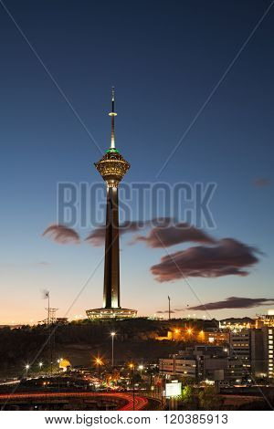 Milad Tower In The Skyline Of Tehran At Dusk Against Cloudy Blue Sky