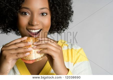 Happy Young Woman Eating Burger
