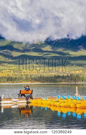 On the mooring there is elderly woman with camera. The wooden boat mooring with the moored boats. Cumulus clouds over the Pyramid mountain and Pyramid Lake