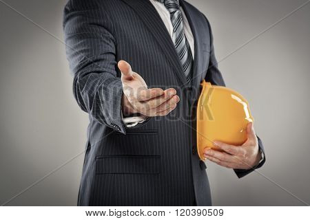 Portrait of male architect with safety hardhat greeting his partner. Young man builder showing handshake. Partnership concept.