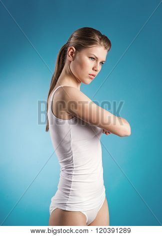 Physical treatment. Young girl doing exercise on painful back over blue background.