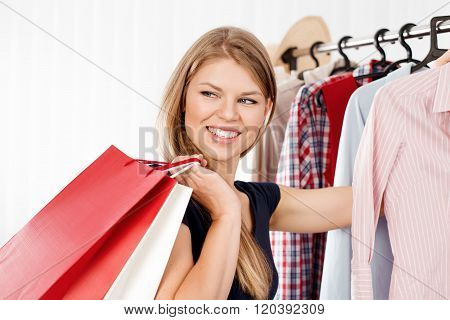 Young joyful woman with colorful shopping bags indoors in retail store. Spree female shopper choosing dress in clothing shop.