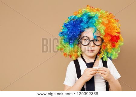 Close-up Portrait Of Little Boy In Clown Wig And Eyeglasses