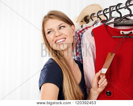 Seasonal sales. Young female customer buying clothes in shopping mall. Happy smiling Caucasian woman holding price tag indoors in store.
