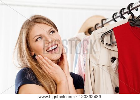 Female shopaholic dreaming of new clothes standing at rack. Pretty smiling Caucasian girl shopping in retail store.