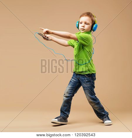 Handsome Little Stylish Boy In Headphones Holding Mp3 Player And Dancing