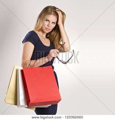 Fancy young woman model with shopping bags holding glasses