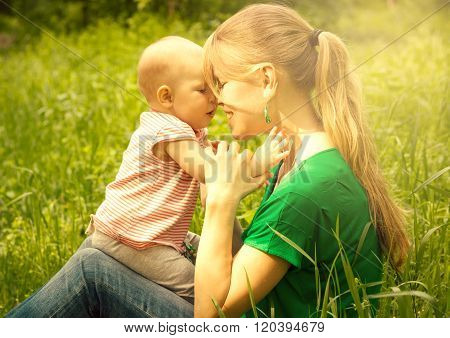 Childcare. Smiling mother holding her cute baby outdoors