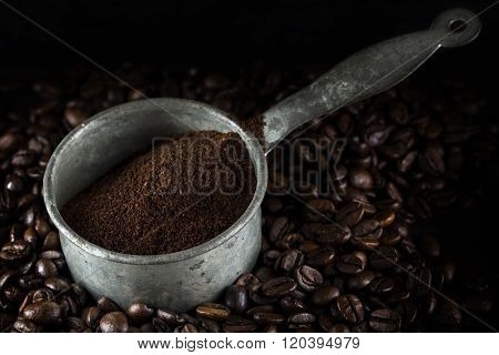 Small Metal Pot With Ground Coffee On Dark Roasted Coffee Beans,  Closeup