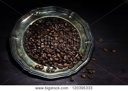 Roasted Coffee Beans On An Old Silver Plate On A Dark Brown Wooden Background, Close Up