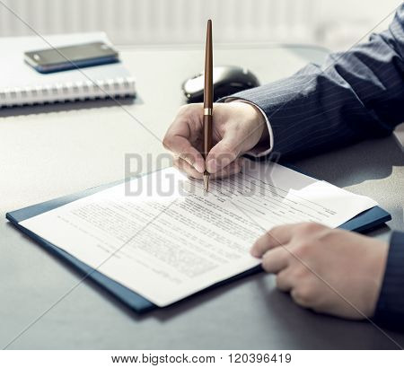 Financial planner signing annual report in company's office