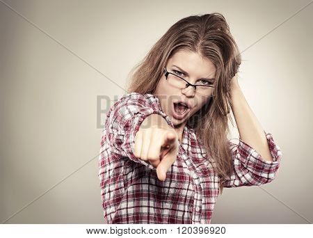 Beautiful screaming woman pointing forefinger at you