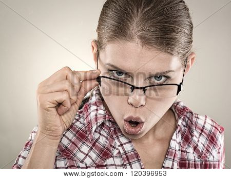 Surprised businesswoman with wide opened eyes touching glasses.