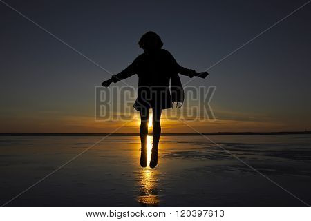 Girl Jumping From The River Ice At Sunset