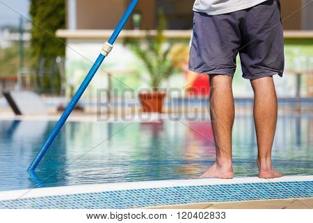 Man Cleaning The Swimming Pool