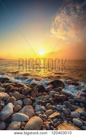 Tropical colorful sunrise at the stones beach